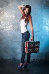 Beautiful young woman with suitcase with British flag