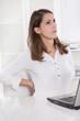 Frau in Weiß hat Rückenschmerzen in der Arbeit