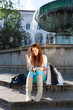 Woman sitting in front of fountain