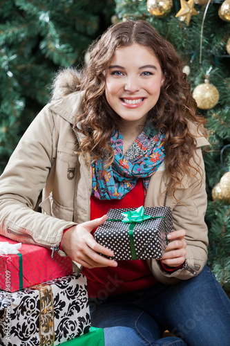 Happy Woman With Presents Sitting Against Christmas Tree