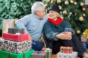 Couple Sitting With Presents In Christmas Store