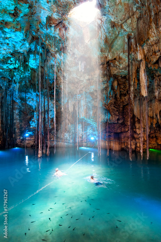 Cenote Dzitnup, Mexico. Blurred couple swimming