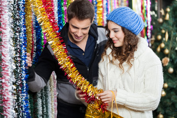 Couple Shopping For Tinsels At Store