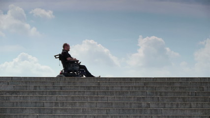 disabled person in a wheelchair on top of an inaccessible stairc
