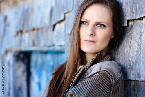 Beautiful woman leaning on a cabin log