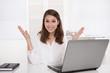 Erfolgreiche lachende junge Frau sitzend im Büro mit Laptop