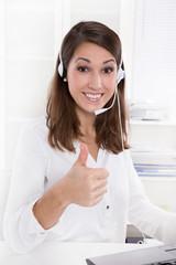 Junge Frau mit Headset - Freude am Job - Daumen hoch