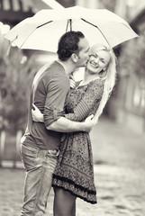 happy couple kissing under the rain
