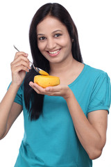 Young indian woman holding ripe mango and teaspoon against white