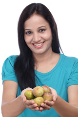 Happy young woman holding ripe figs in her hands