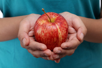 Closeup of hands holding fresh red apple