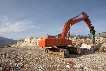 Orange backhoe drilling stone soil on construction of road