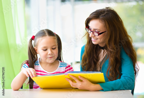 Mother is reading book with her daughter