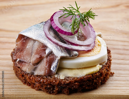 brown bread canape with anchovies decorated with red onion and d