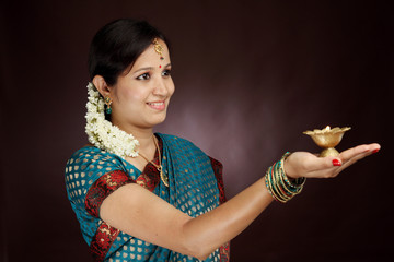 Traditional young woman holding diwali diya