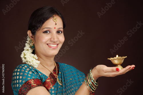 Beautiful traditional woman holding oil lamp light