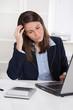 Junge Frau sitzend am Schreibtisch hat Kopfschmerzen