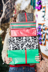 Woman Hiding Behind Stack Of Christmas Gifts