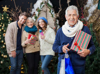 Happy Family With Christmas Presents And Shopping Bags At Store