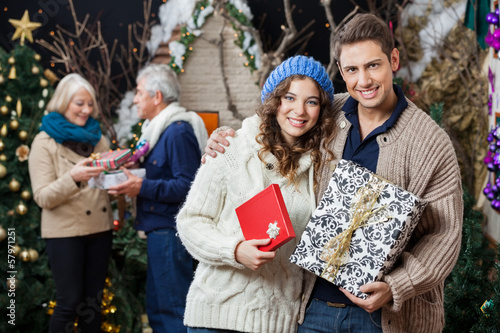Happy Couple Holding Christmas Presents With Parents In Backgrou