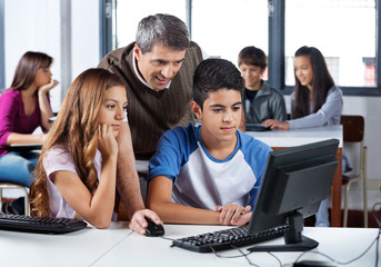 Male Teacher Assisting Students In Computer Class