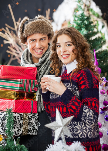 Young Couple With Disposable Cups And Christmas Presents