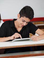 Happy Teenage Schoolboy Using Tablet At Desk
