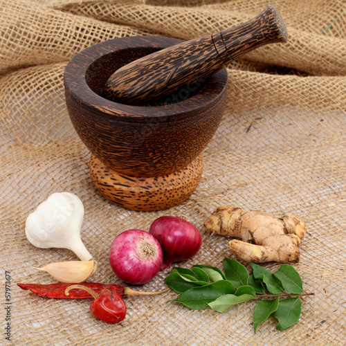 Wooden mortar with various spices on sacking