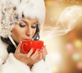 A beautiful woman with a red cup on a Christmas background