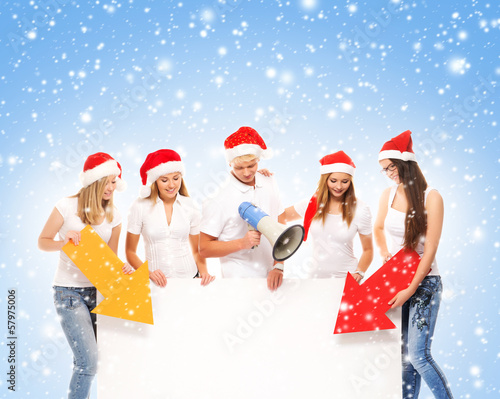 A group of teenagers in Christmas hats pointing on a banner