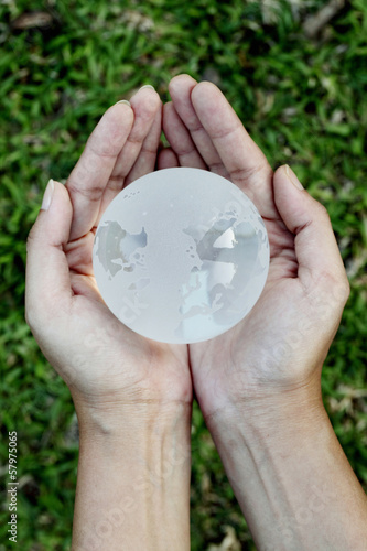 Hands holding a glass globe against green