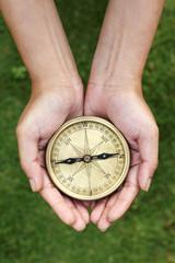 Hands holding navigational compass