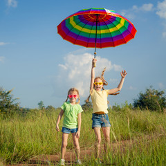 Two Girls jumping on the road with an umbrella