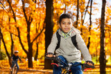 Brothers ride a bike in autumn park
