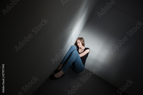 Depressed woman sitting on the floor (color toned image)