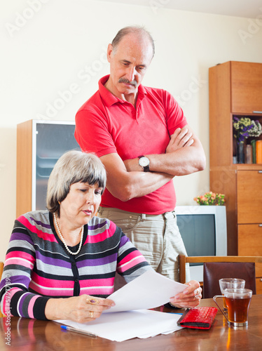 mature couple reading financial document