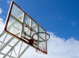 Dark basketball hoop and net against blue sky