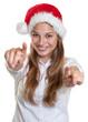 Lachende Frau mit Nikolausmütze zeigt mit Fingern