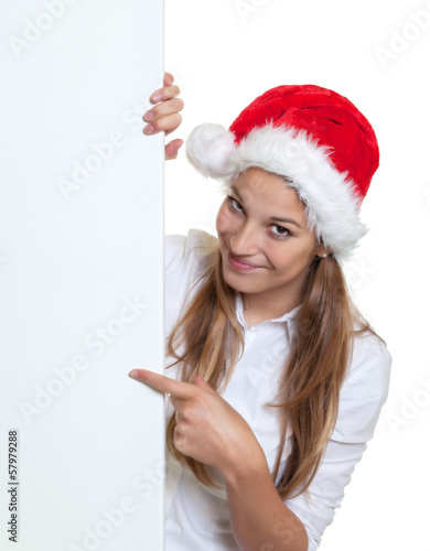 Beautiful woman with christmas hat pointing on a signboard