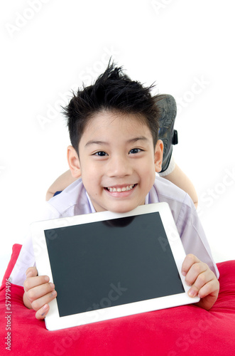 Little asian boy in student's uniform with tablet computer on is