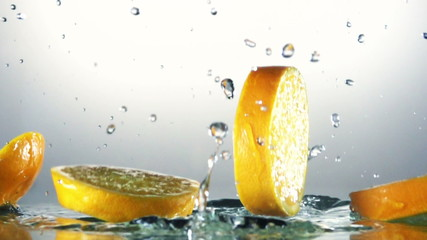 Orange splashing into water, slow motion