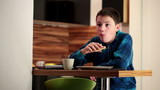 Boy eating sandwich and drinking tea at the kitchen table
