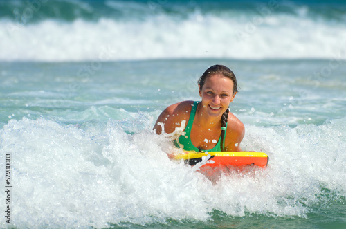 Young attractive woman bodyboards on surfboard with nice smile