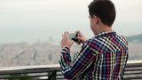 Boy taking picture of city view with his smartphone
