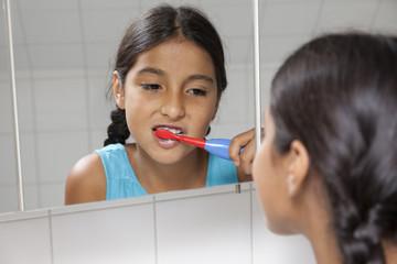 Young teenage girl brushing her teeth