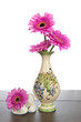 Pink Gerbera in decorated vase and white stones