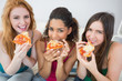 Portrait of happy female friends eating pizza at home