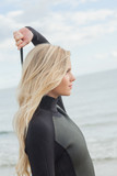Side view of a blond in wet suit standing at beach
