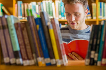 Student reading a book amid bookshelves in the library
