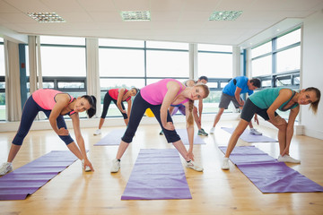 People stretching hands at yoga class in fitness studio